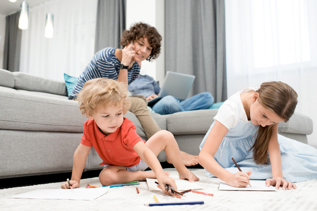 Portrait-of-two-children-drawing-pictures-sitting-on-carpet-in-living-room-with-mom-watching-them-fr